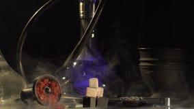 Vue en gros plan horizontale de composition se composant de l'équipement de fumée, braises et changeant le narguilé de couleurs e banque de vidéos