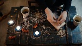 Vue en gros plan supérieure des mains femelles faisant le cadeau se reposant à la table à la maison La femme lie une boîte de Noë banque de vidéos