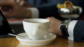 Vue en gros plan sur des mains des hommes avec le comprimé et le café avec le dessert banque de vidéos