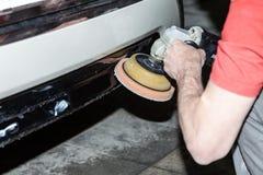 Vue en gros plan sur les mains d'un travailleur de sexe masculin qui tient un outil pour polir le pare-chocs d'une voiture tout e photographie stock