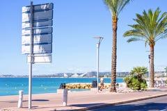 Vue ensoleillée de lumière du jour à la ville, à la mer bleue et à la femme courant sur le sidew Images stock