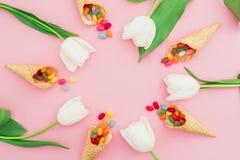Vue faite de sucrerie lumineuse en cônes de gaufre et fleurs blanches de tulipe sur le fond rose Configuration plate, vue supérie Image stock