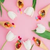 Vue faite de sucrerie de sucre en cônes de gaufre et fleurs blanches de tulipe sur le fond rose Configuration plate, vue supérieu Photos libres de droits