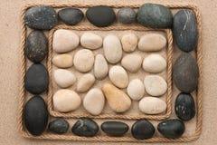 Vue faite en corde se trouvant sur le sable parmi les pierres noires et blanches Images libres de droits
