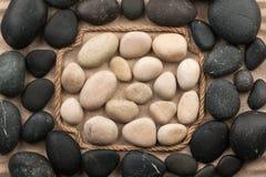 Vue faite en corde se trouvant sur le sable parmi les pierres noires et blanches Photos stock