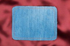 Vue faite en tissu de denim avec piquer jaune sur la soie rouge Photos stock