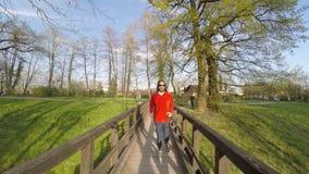 Vue frontale de l'homme fonctionnant en bas du pont en parc, mouvement lent banque de vidéos
