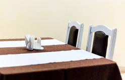 Vue générique de table de restaurant avec la table couverte par des serviettes d'anf de nappe là-dessus Image libre de droits