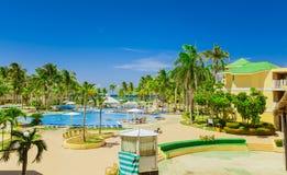 Vue gentille des au sol d'hôtel, du jardin tropical et des diverses piscines avec la détente de personnes Photographie stock