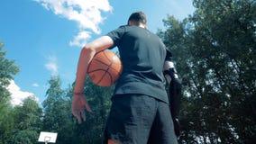 Vue grande-angulaire d'un homme avec une main artificielle se tenant dans un au sol de sports avec une boule