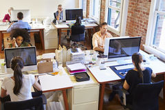 Vue grande-angulaire de bureau de conception occupé avec des travailleurs aux bureaux Images stock