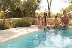 Vue grande-angulaire de famille des vacances détendant par la piscine photos stock