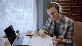 Vue haute étroite d'un jeune guitariste essayant de composer sa nouvelle chanson dans une pause-café duting abandonnée de café Ap banque de vidéos