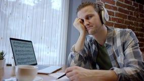 Vue haute étroite d'un jeune musicien fatigué essayant de composer sa nouvelle chanson dans une pause-café duting abandonnée de c banque de vidéos
