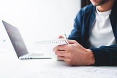 Vue haute étroite de bloc-notes de prise de main d'homme d'affaires tout en travaillant au bureau et à l'aide du carnet photos libres de droits