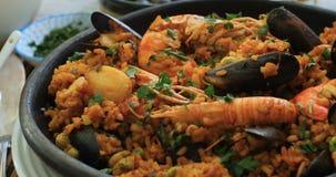 Vue haute étroite de chariot d'une Paella espagnole de fruits de mer : moules, crevettes roses de roi, langoustine, aiglefin banque de vidéos