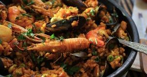 Vue haute étroite de cuisson de chariot d'une Paella espagnole de fruits de mer : moules, crevettes roses de roi, langoustine banque de vidéos