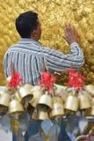 Vue haute étroite de verticale de pèlerin collant soigneusement des feuilles d'or sur la roche d'or à la pagoda de Kyaiktiyo avec Photographie stock