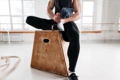 Vue haute étroite sur l'athlète masculin fort se reposant sur la boîte en bois après la croix intense dans le gymnase de séance d image stock