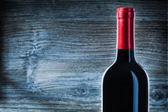 Vue haute étroite sur la bouteille avec le vin rouge sur le bois de cru photos stock