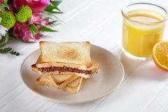 Vue haute ?troite sur le pain grill? avec le beurre d'arachide Concept de petit déjeuner avec du jus, les fleurs et le sandwich d image libre de droits