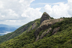 Vue horizontale d'un visage de roche de montagne avec quelques arbres sous un ciel bleu avec les nuages blancs - le serra du pico image libre de droits