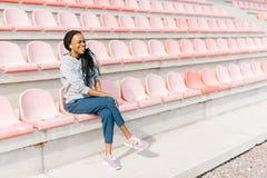 Vue horizontale de l'adolescent afro-américain riant observant la manifestation sportive sur le stade Images stock