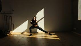 Vue horizontale de la femme sportive faisant des mouvements brusques latéraux dans la salle mal allumée banque de vidéos