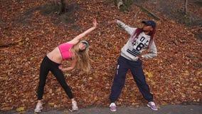 Vue horizontale des deux amies multiculturelles abaissant et de côté de recourbement pour dégrossir en parc d'automne banque de vidéos