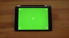 Vue horizontale en gros plan de approche de comprimé avec l'écran vert sur le fond en bois de bureau banque de vidéos