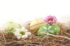 Vue horizontale rurale des oeufs de pâques dans le foin avec des fleurs d'isolement Image libre de droits