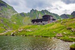 Vue idyllique avec la loge typique sur le rivage de lac Balea à Fagaras M Image stock
