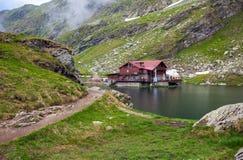 Vue idyllique avec la loge typique sur le rivage de lac Balea à Fagaras M photographie stock