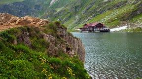 Vue idyllique avec le cottege sur le rivage de lac Balea à Fagaras Mountai Photos stock