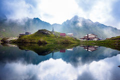 Vue idyllique avec les loges typiques sur le rivage de lac Balea à Fagaras Image stock