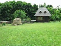 Vue idyllique de petite maison sur un fond des fleurs et du vert Images stock