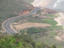 Vue impressionnante de route avec la plage de mer des collines semblant bonnes Photographie stock libre de droits