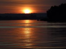 Vue incroyable de coucher du soleil près de la rivière le soleil rayonne la réflexion photographie stock libre de droits