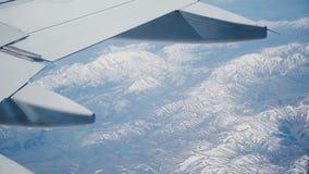 Vue incroyable de siège fenêtre d'avion au milieu du vol, volant au-dessus de stupéfier les arêtes neigeuses de crête de montagne banque de vidéos