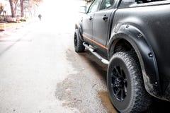 Vue inférieure à la grande roue de voiture tous terrains sur le contexte de route de campagne photographie stock
