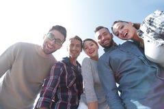 Vue inférieure équipe d'amis regardant l'appareil-photo Photographie stock
