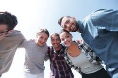 Vue inférieure équipe d'amis regardant l'appareil-photo Photos stock