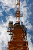 Vue inférieure de grue jaune avec la cabine et le ciel bleu Photographie stock