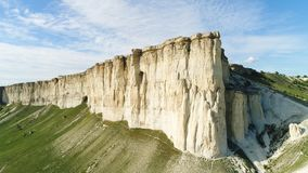 Vue inférieure de la haute roche blanche sur le fond bleu de ciel nuageux projectile Jour ensoleillé et beau pré vert au pied image stock