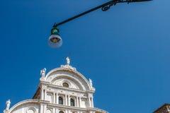 Vue inférieure de réverbère traditionnel et d'une vieille église vénitienne célèbre dans le milieu de la journée avec un bleu Image stock