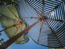 Vue inférieure des parapluies de plage rayés colorés multicolores contre le ciel et image libre de droits
