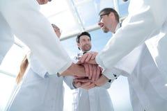 Vue inférieure la fin de l'des médecins a plié leurs mains ensemble Photo stock