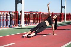 Vue intégrale d'une femme sportive merveilleuse sur une position latérale de planche photo stock