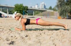 Vue intégrale de fille blonde sportive dans le maillot de bain sur une position de planche à la plage photos stock
