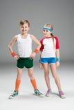 Vue intégrale de garçon et de fille de sourire mignons dans les vêtements de sport se tenant ensemble sur le gris Photos libres de droits